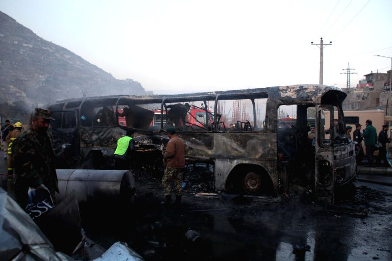 Afghan security forces gather around a burned army bus which was targeted by a suicide bomber in Kabul, Afghanistan, Dec, 13, 2014. A suicide bomber blew himself up next to a bus carrying army