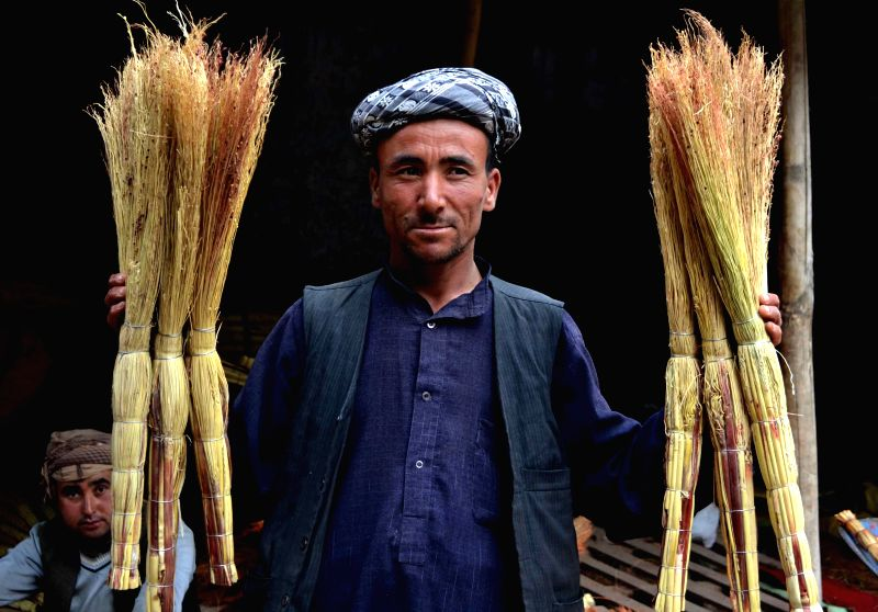 A man holds brooms at a shop in Kabul, Afghanistan, on April 19, 2014.