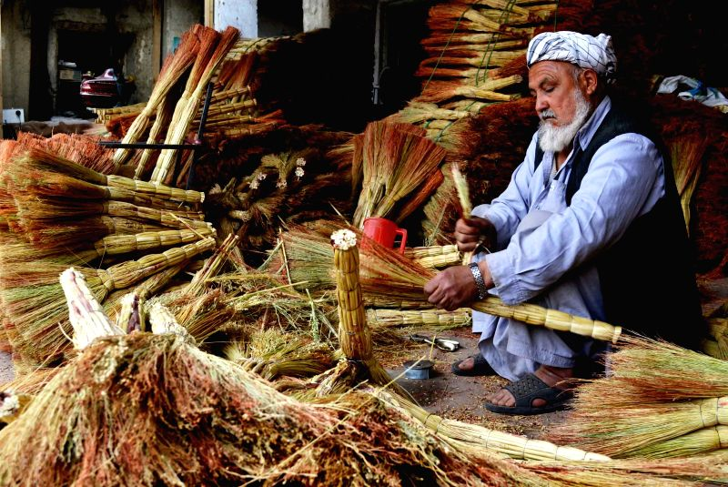 A man makes brooms at a shop in Kabul, Afghanistan, on April 19, 2014.