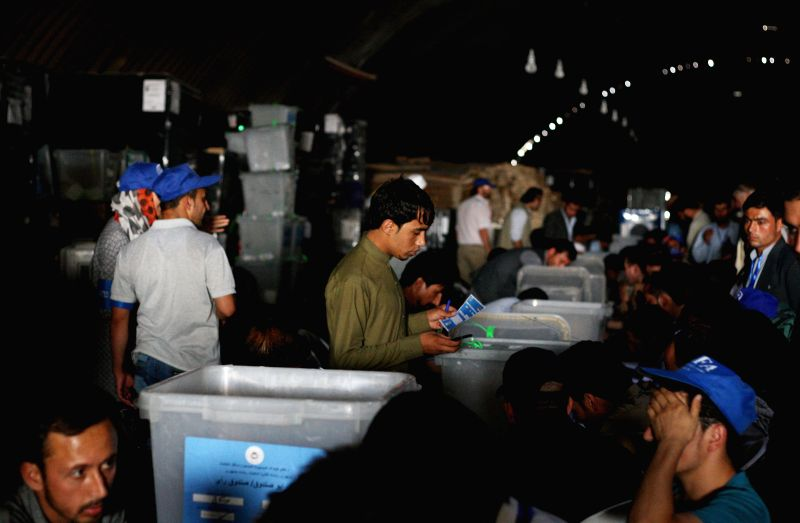 Afghan election commission workers count ballots during an audit of the presidential run-off votes at an election commission warehouse in Kabul, Afghanistan, on ...