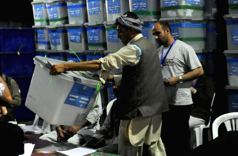 An Afghan election commission worker carries a ballot box during an audit of the presidential run-off votes at an election commission warehouse in Kabul, Afghanistan,