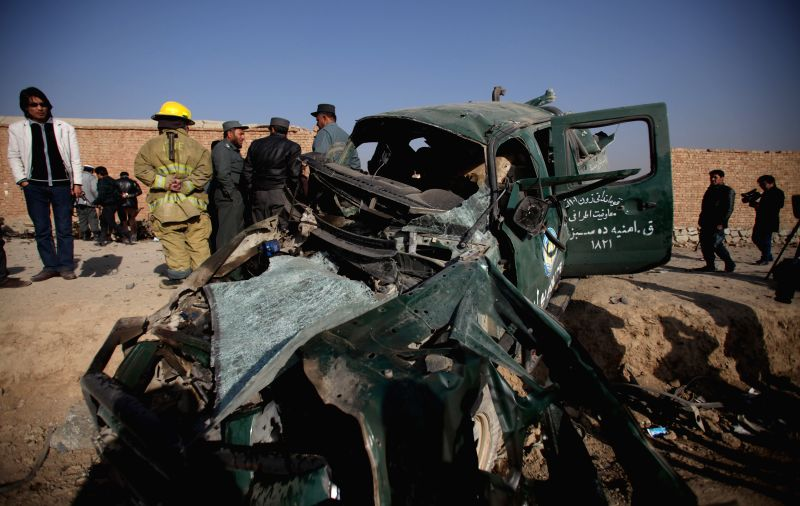 Policemen gather around a destroyed police vehicle following a car bombing in Kabul, Afghanistan, on Dec. 18, 2014. One policeman was killed and three others were ...