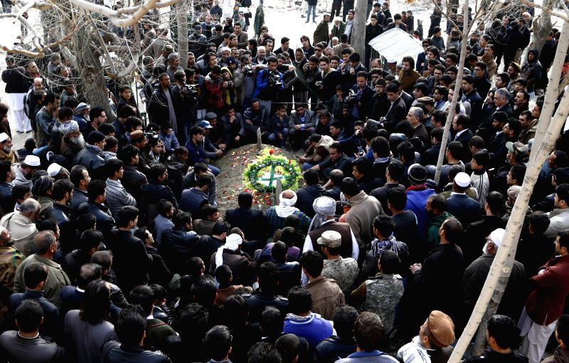 People pray at the grave of Afghan journalist Zubair Hatami, who died from injuries sustained in a Taliban attack, during his funeral ceremony in Kabul, Afghanistan, .
