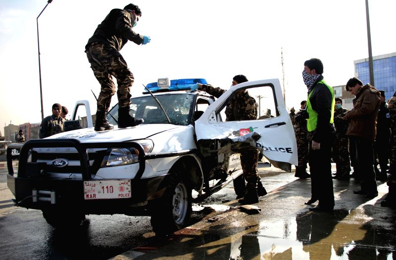 Afghan security forces investigate a damaged police vehicle following a blast in Kabul, capital of Afghanistan, on Dec. 28, 2014. A bomb planted on the vehicle of ...