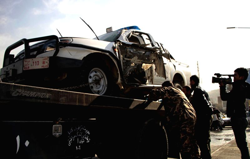 Afghan security forces gather around a damaged police vehicle following a blast in Kabul, capital of Afghanistan, on Dec. 28, 2014. A bomb planted on the vehicle of ..