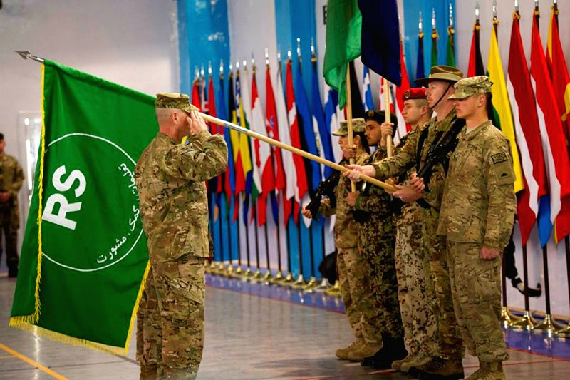 Members of the NATO-led International Security Assistance Force (ISAF) soldiers hold the flag of Resolute Support (RS) during a ceremony marking the end of ISAF's ...