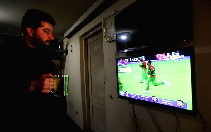 An Afghan cricket fan watches a live broadcast of the ICC Cricket World Cup 2015 Match between Afghanistan and Bangladesh in Kabul, Afghanistan, Feb. 18, 2015. ...