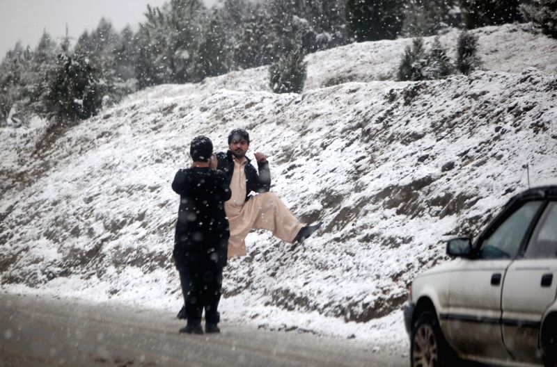A man takes photos of his friend in a heavy snow in Kabul, Afghanistan, Feb. 24, 2015.