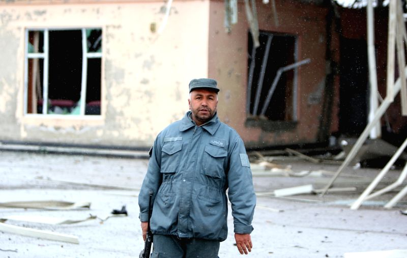 An Afghan policeman stands guard following a suicide car bombing in Kabul, Afghanistan, Jan. 25, 2015. One attacker was killed and two civilians were wounded after a .