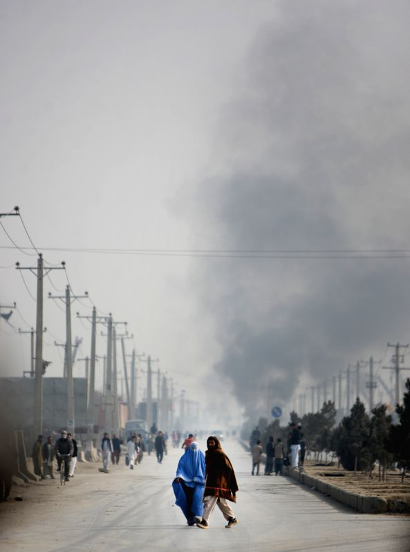 Afghan people walk while smoke rises during an angry protest against caricatures published in French magazine Charlie Hebdo in Kabul, Afghanistan on Jan. 31, 2015. At