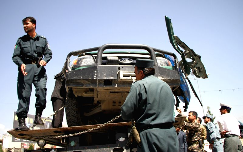 Afghan policemen remove a destroyed police vehicle from the site of blast in Kabul, Afghanistan, July 10, 2014. Earlier in the day, one civilian and one police were ..