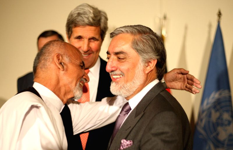 Presidential candidate Abdullah Abdullah (R) embraces with presidential candidate Ashraf Ghani Ahmadzai after a joint press conference in Kabul, Afghanistan, on July .