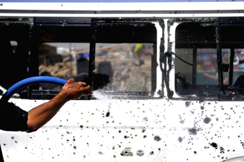 An Afghan man washes a damaged bus at the blast site in Kabul, Afghanistan, July 15, 2014. At least two people were killed while five others were wounded in the bomb .
