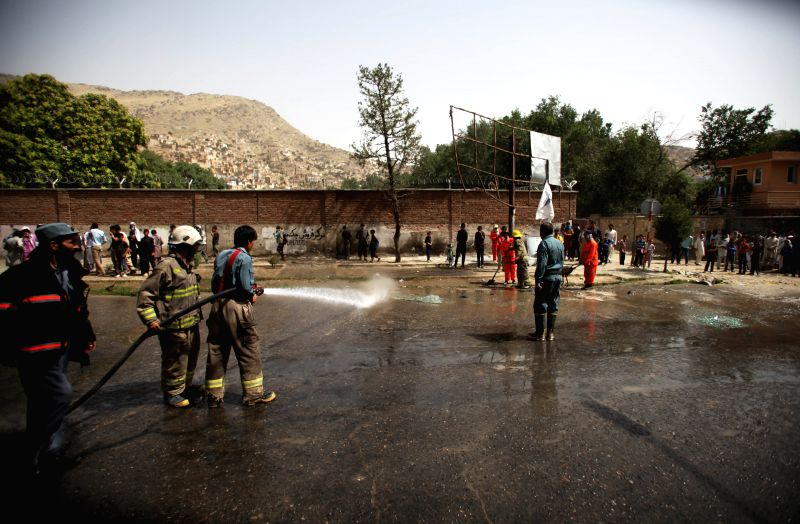 Afghan fire fighters wash the site of suicide bombing in Kabul, Afghanistan, July 2, 2014. At least five army personnel were killed and nine people wounded after a ...