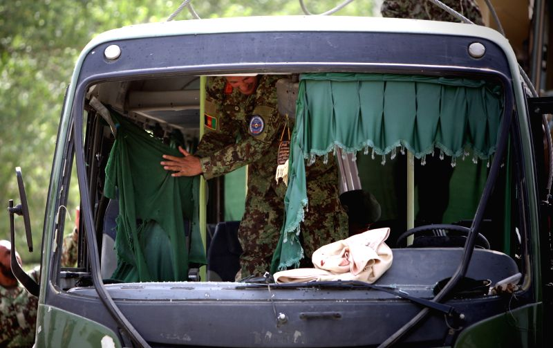 Afghan security forces investigate inside a damaged bus at the site of suicide bombing in Kabul, Afghanistan, July 2, 2014. At least five army personnel were killed ...
