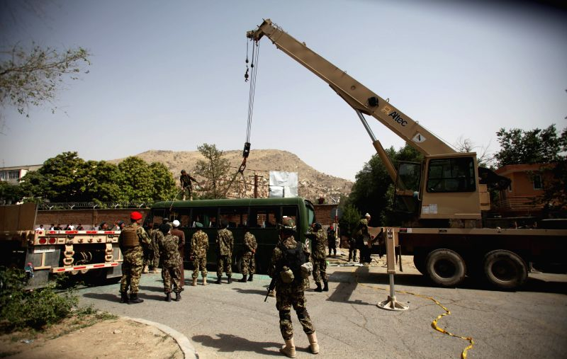 Afghan soldiers remove the damaged bus at the site of suicide bombing in Kabul, Afghanistan, July 2, 2014. At least five army personnel were killed and nine people ...