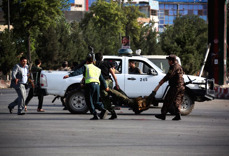 KABUL, July 22, 2018 - Afghan security force members carry an injured man at the site of an attack in Kabul, capital of Afghanistan, July 22, 2018. Over two dozen people including civilians and ...