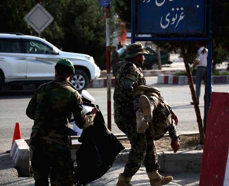 KABUL, July 22, 2018 - An Afghan security force member carries an injured man at the site of an attack in Kabul, capital of Afghanistan, July 22, 2018. Over two dozen people including civilians and ...