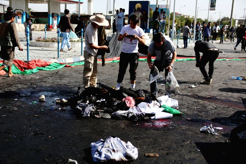 KABUL, July 23, 2016 - People collect the belongings of the victims at the site of a blast in Kabul, capital of Afghanistan, July 23, 2016. At least 61 people were killed and some 207 others wounded ...