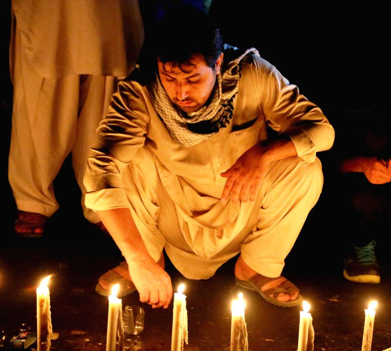 KABUL, July 24, 2016 - An Afghan man attends a candlelight vigil to commemorate victims of a suicide attack in Kabul, capital of Afghanistan, July 23, 2016. At least 80 people were killed and more ...