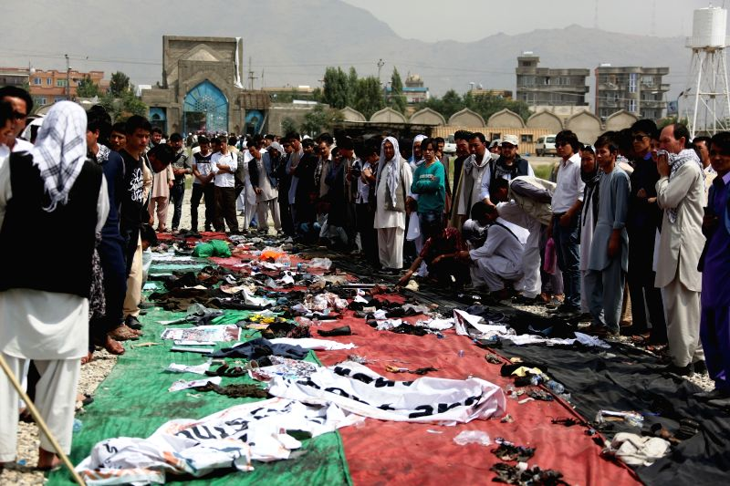 KABUL, July 24, 2016 - People look at the belongings of the victims of a suicide attack in Kabul, capital of Afghanistan, July 24, 2016. At least 80 people were killed and more than 200 others ...