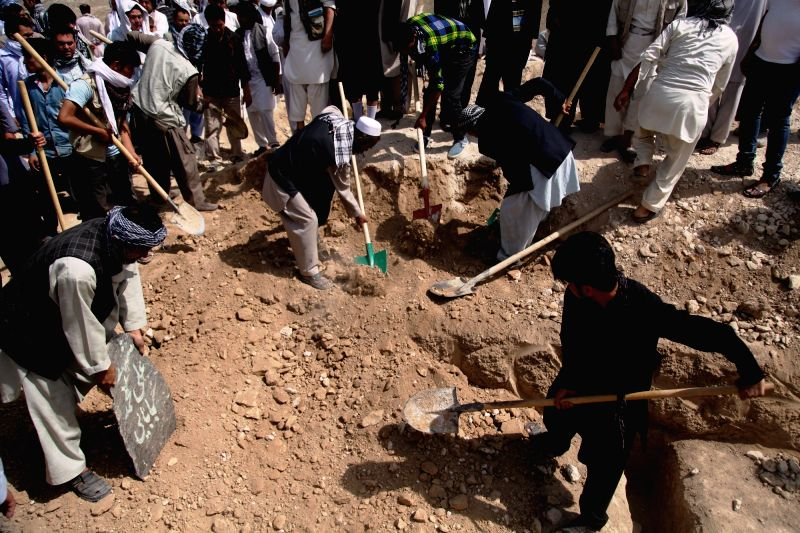 KABUL, July 25, 2016 - People shovel earth on the tomb of a victim of a suicide attack during a funeral ceremony in Kabul, capital of Afghanistan, July 25, 2016. At least 80 people were killed and ...