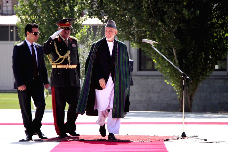 Afghan president Hamid Karzai (R) reviews honor guards before the Eid al-Fitr prayer in Kabul, Afghanistan, on July 28, 2014. President Hamid Karzai offered Eid ...