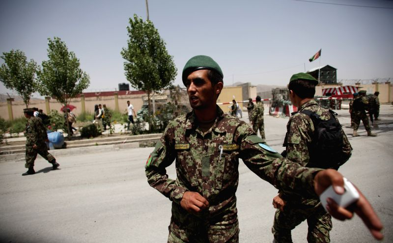 Afghan National Army soldiers stand guard outside the entrance of a military airport in Kabul, Afghanistan, on July 3, 2014. Two rockets slammed into Kabul airport on .