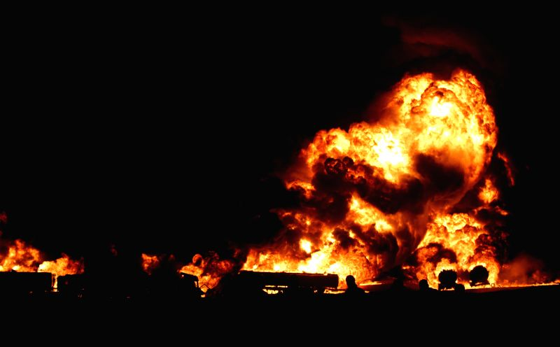 Flames rise from oil tanker trucks hit by rockets in Kabul, Afghanistan, July 5, 2014. Oil tanker trucks were hit by rockets fired by militants in Kabul on Saturday. ..