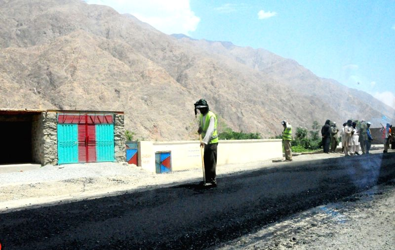 Afghan men work at Kabul-Balkh Highway in Baghlan province, northern Afghanistan, June 19, 2014. More than 10,000 kilometers highway and main roads had been ...