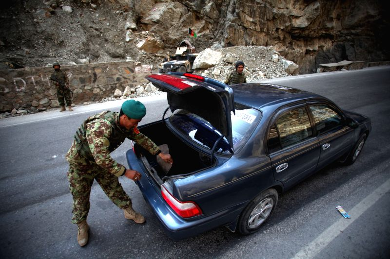 An Afghan National Army soldier searches a vehicle next to an army checkpoint in Sourbi district of Kabul, Afghanistan, March 14, 2015. Some nine militants have been ...