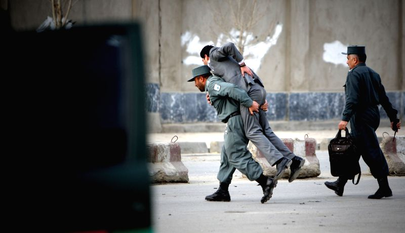 An Afghan policeman carries a wounded man from the site of a suicide bombing in Kabul, Afghanistan, March 25, 2015. The suicide bombing that rocked Kabul city on ...