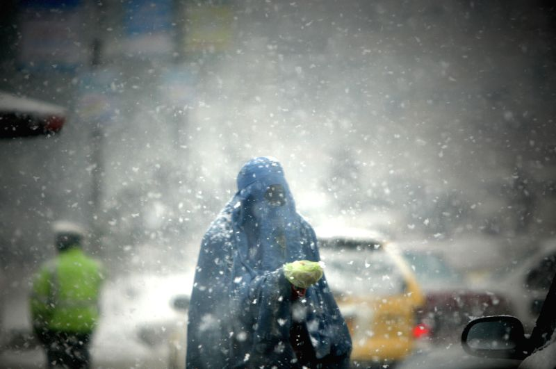 An Afghan woman begs along a road during a heavy snowfall in Kabul, capital of Afghanistan, on March 4, 2015.