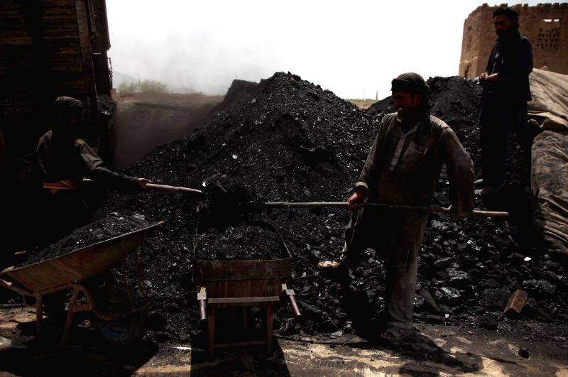 Afghan labors load coal into a cart at a factory on the International Labor Day in Kabul, Afghanistan, May 1, 2014. At least 17 people were killed while several workers