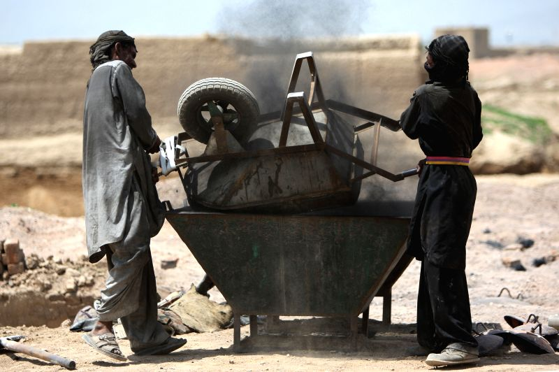 Afghan labors unload coal at a factory on the International Labor Day in Kabul, Afghanistan, May 1, 2014. At least 17 people were killed while several workers trapped ..