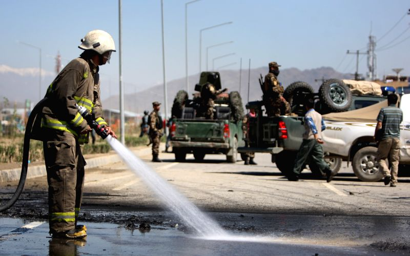 A firefighter cleans the site of blast in Kabul, Afghanistan, May 13, 2015. An explosion targeted a police vehicle in the Afghan capital of Kabul on Wednesday, causing ...