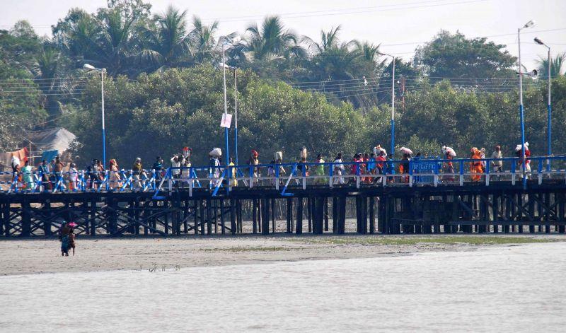 Pilgrims proceed to board a ferry for Gangasagar island in Kakdwip, 110 km south of Kolkata on Jan 12, 2015.