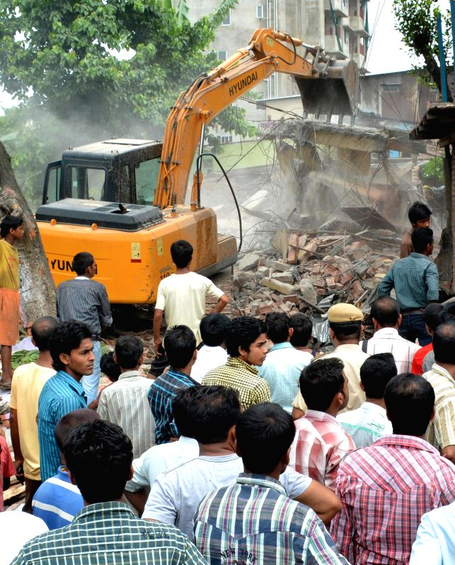 Kamrup Metropolitan district administration carries on a demolition drive against illegal sturctures along the Bharalu River near Sarab Bhatti in Guwahati on July 3, 2014.