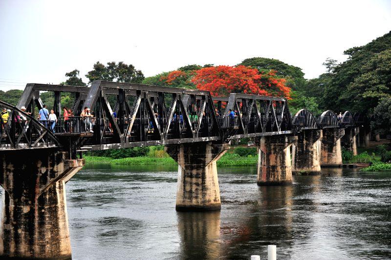 "Tourists walk along the rebuilt ""Bridge on the River Kwai"" in Kanchanaburi Province, Thailand, April 30, 2014. The original ""Bridge on the ..."