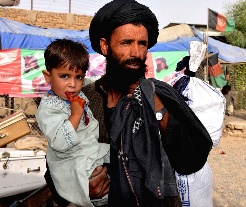 KANDAHAR, Aug. 2, 2016 - An Afghan man returning from Pakistan holds his child at the Spin Buldak border of southern Kandahar province, Afghanistan, Aug. 2, 2016. The United Nations refugee agency ...