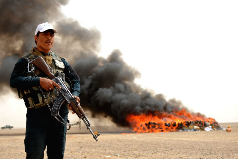 KANDAHAR, March 13, 2018 - An Afghan security force member stands guard beside burning drugs in Daman district of southern Kandahar province, Afghanistan, March 13, 2018. Afghan authorities burned ...