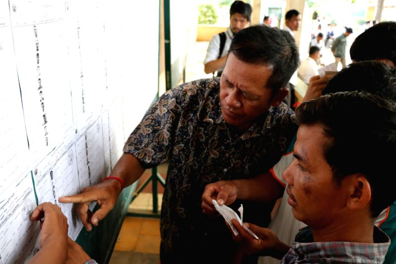 KANDAL, July 29, 2018 - Voters check the name list at a polling station in Kandal, about 15 km south of capital Phnom Penh, Cambodia, on July 29, 2018. The sixth general election kicked off in ...
