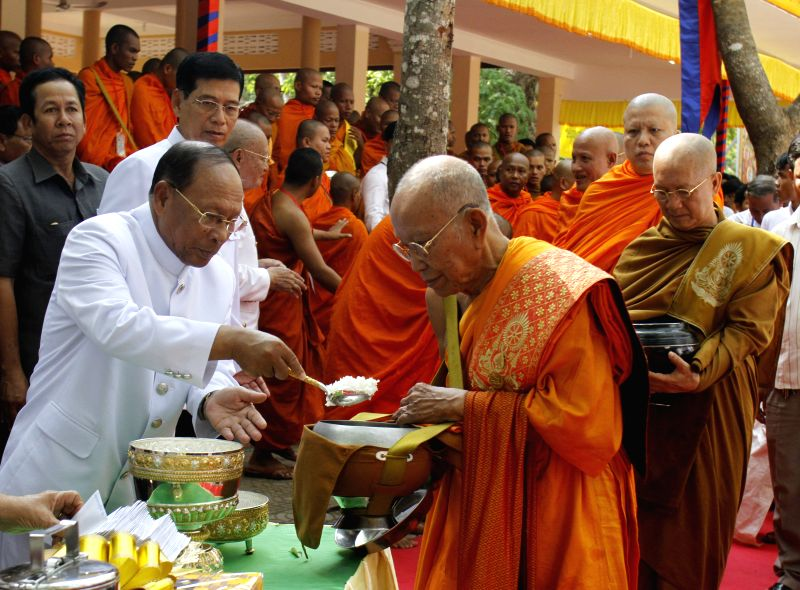 Cambodian Parliament chief Heng Samrin (L, front) gives food to Buddhist monks on the Visak Bochea Day in Kandal province, Cambodia, May 2, 2015. Cambodia on Saturday ...