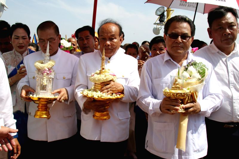 KANDAL, May 20, 2016 - Cambodian Minister of Cults and Religion Him Chhem (C, front) carries the golden urn containing relics of the Buddha at Oudong Mountain in Kandal province, Cambodia, on May 20, ...