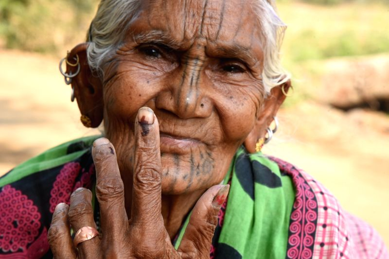 Kandhamal: An elderly woman shows her forefinger marked with indelible ink after casting vote during the second phase of Lok Sabha polls, in Odisha's Kandhamal, on April 18, 2019. (Photo: IANS)