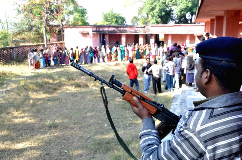 A soldier stands guard as people cast their votes during the third phase of Jharkhand assembly polls n Maoist infested Sukurhutu village near Kanke in Ranchi on Dec 9, 2014.