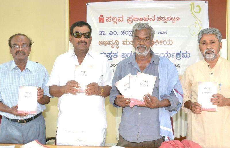 Kannada litterateur and social activist Devanoor Mahadeva with Dr. TR Chandrashekar, former legislator Sriramareddy and author Dr. M Chandra Poojari during release of the book 'Abirudi and Rajakiya' .