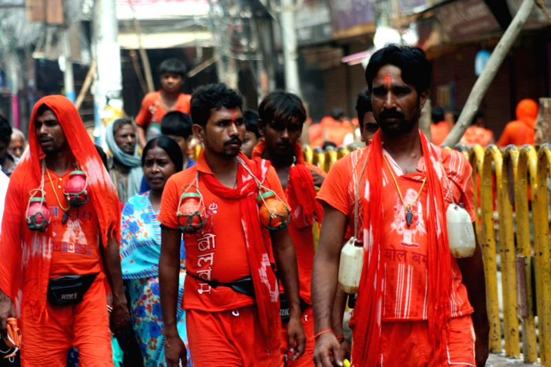 Kanwariyas proceed towards Kashi Vishwanath temple after collecting holy water from the ganges in Varanasi on July 21, 2014.