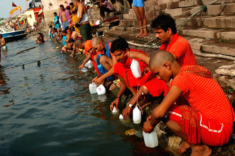 Kanwariyas (worshippers of lord Shiva) collect `jal` - the holy water from Ganga river in their jerrycans which they will be carrying to the Kashi Vishwanath Temple in Varanasi on July 28, 2014.