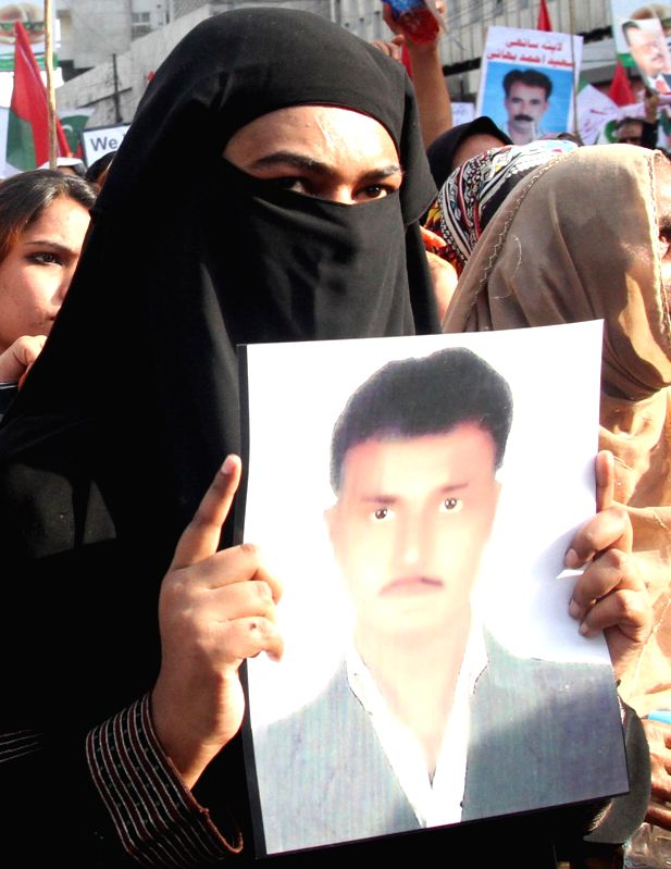 A woman holds a portrait of her missing relative during a protest rally against killing and disappearance of Muttahida Qaumi Movement (MQM) workers in southern ...